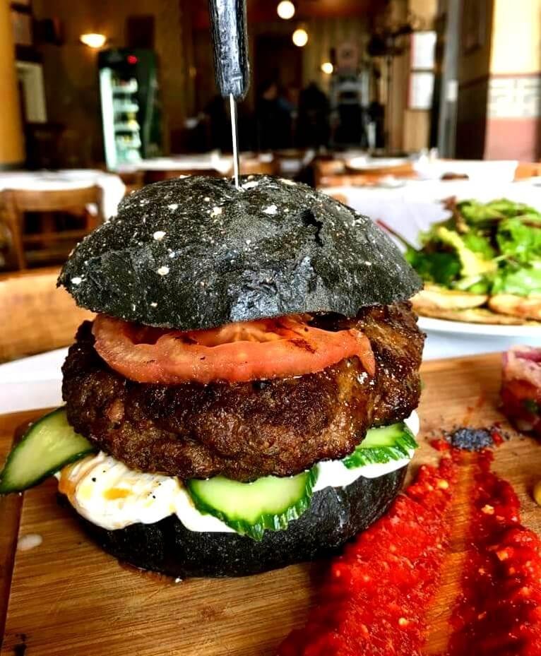 Ελληνικό burger με ψωμί ενεργού άνθρακα, σάλτσα γιαουρτιού, μαριναρισμένο αγγούρι και σάλτσα πιπεριάς Φλωρίνης με φέτα