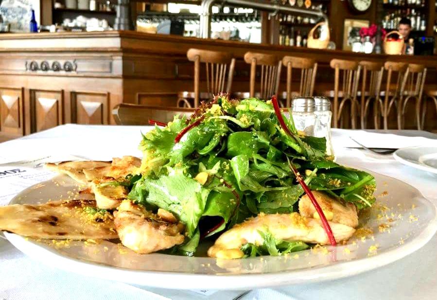 Σαλάτα κοτόπουλο με πράσινα φύλλα, σάλτσα λαδολέμονο με φυστικοβούτυρο, πάνω σε σπιτική ροδίτικη πίτα